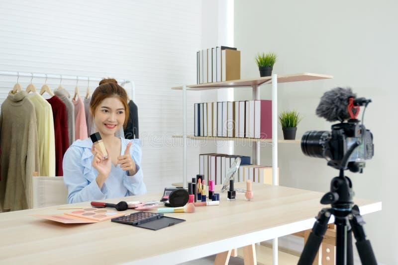 De jonge Aziatische videobloggerduim van de vrouwenschoonheid omhoog en tonend schoonheidsmiddel voor maakt omhoog, het concept v royalty-vrije stock fotografie