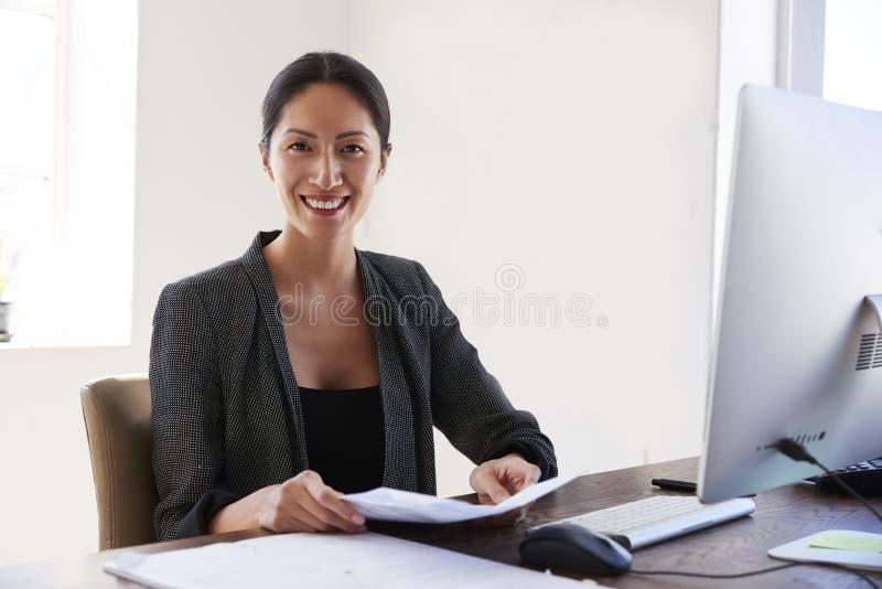 De jonge Aziatische vrouw bij bureauholding documenteert glimlachen aan camera royalty-vrije stock afbeeldingen