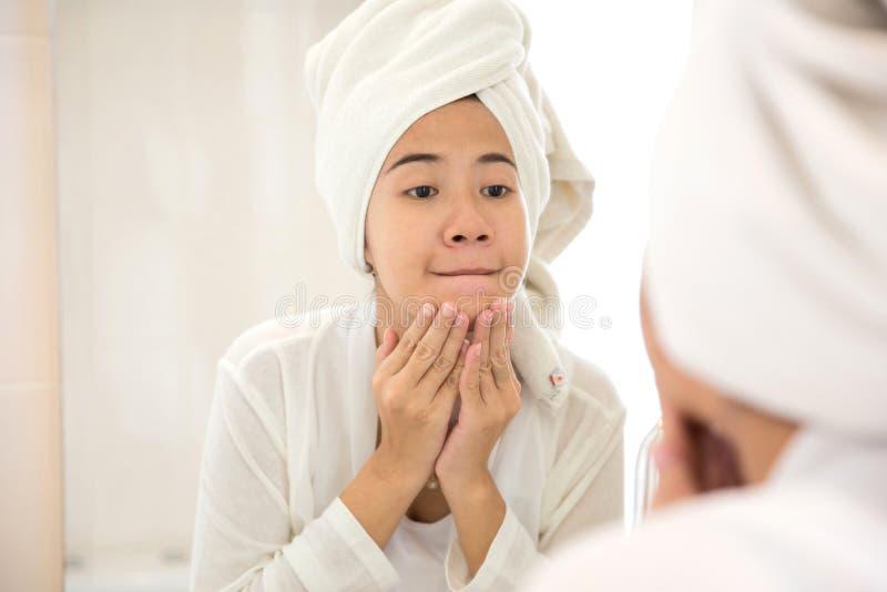 De jonge Aziatische vrouw die haar gezicht, het proberen drukken verwijdert acne stock foto's
