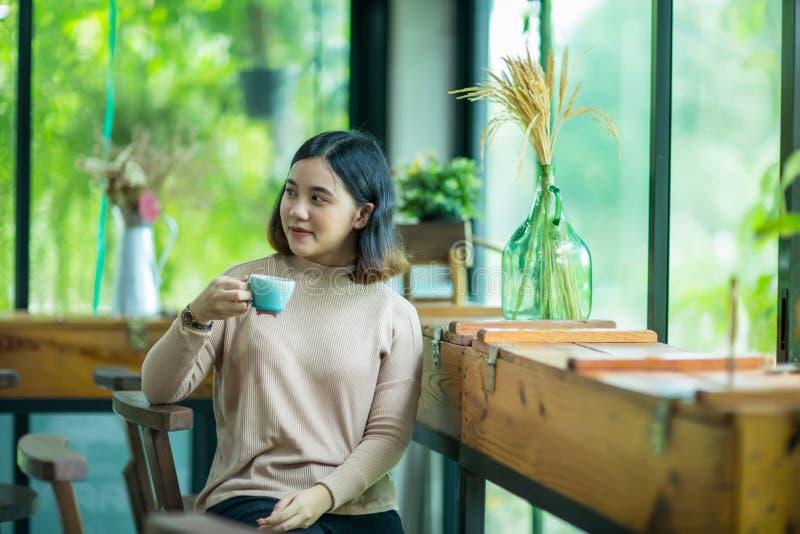 De jonge Aziatische vrouw geniet van met koffie royalty-vrije stock foto