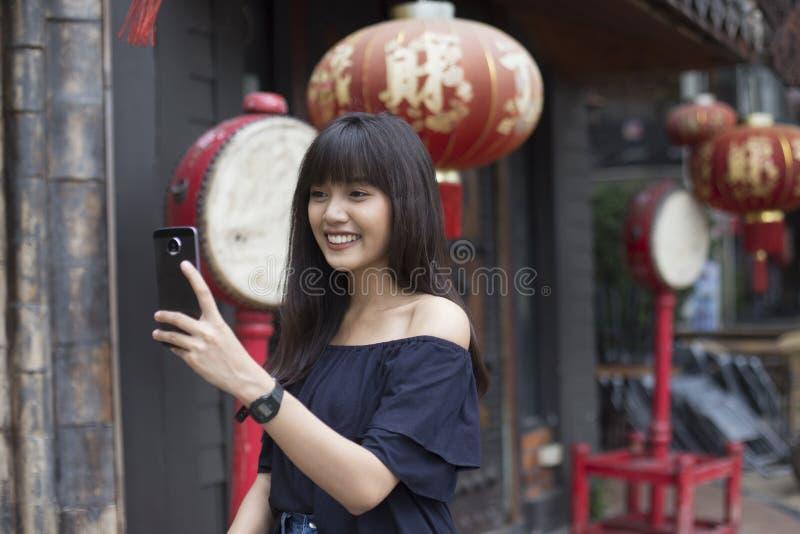 De jonge Aziatische vrouw geniet van met smartphone in de stad van China royalty-vrije stock foto's