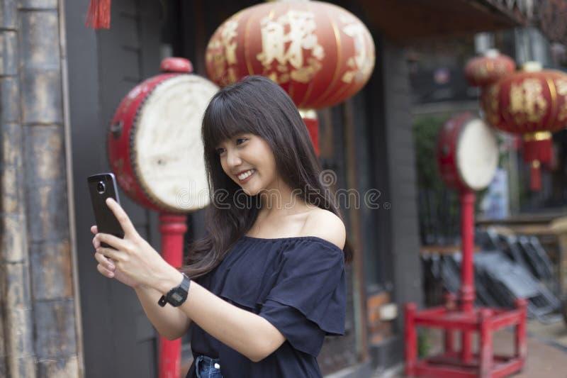 De jonge Aziatische vrouw geniet van met smartphone in de stad van China stock fotografie
