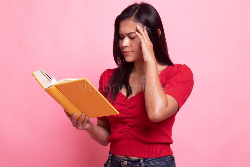 De jonge Aziatische vrouw geworden hoofdpijn las een boek royalty-vrije stock fotografie