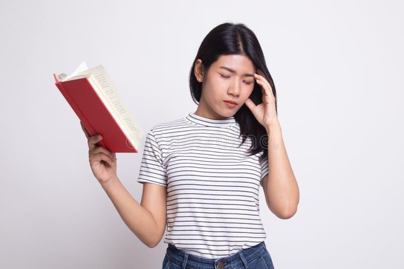 De jonge Aziatische vrouw geworden hoofdpijn las een boek royalty-vrije stock afbeelding