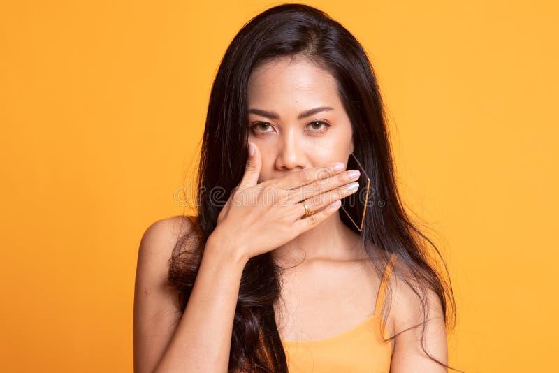 De jonge Aziatische vrouw sluit haar mond met hand royalty-vrije stock afbeelding