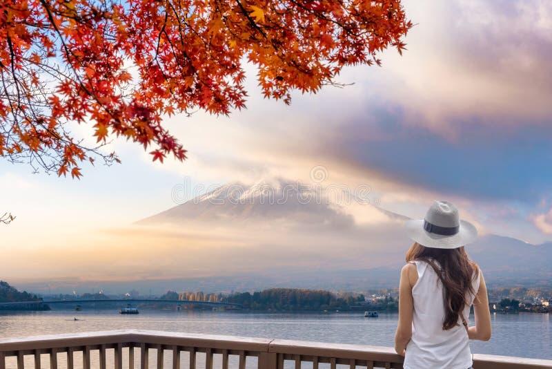 De jonge Aziatische vrouw status op houten balkon die zet fuji-San door mist met rode Esdoorndekking bij op ochtend eruit zien stock foto's