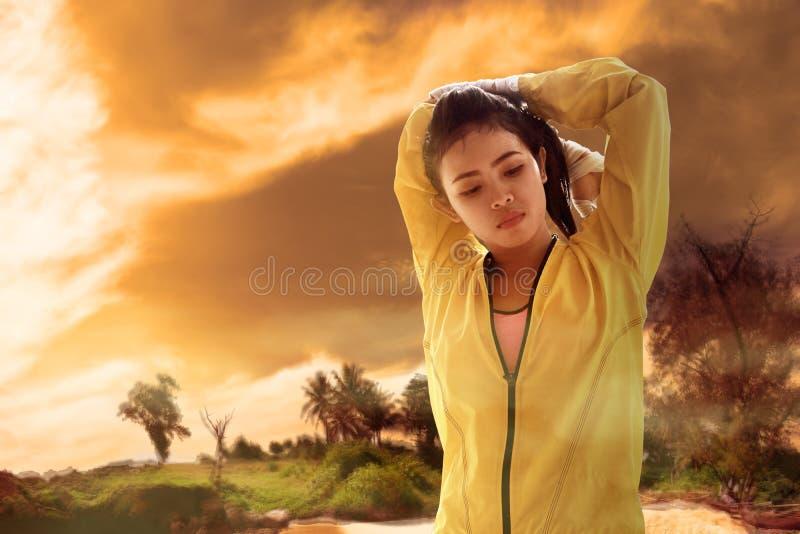 De jonge Aziatische vrouw voelt dehydratie terwijl opleiding stock afbeelding