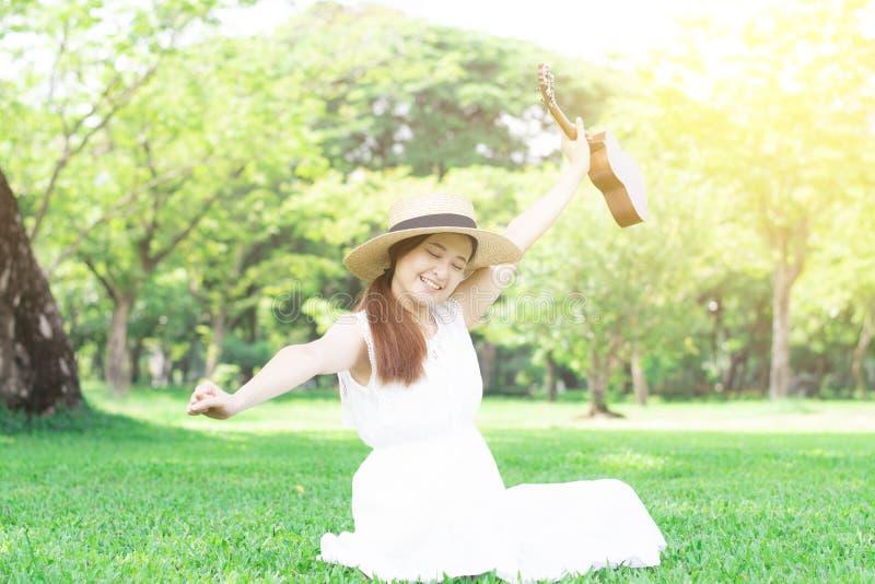 De jonge Aziatische vrouw voelt plezier in het park royalty-vrije stock afbeelding