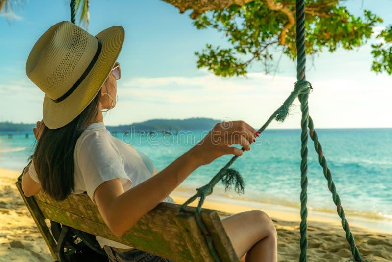 De jonge Aziatische vrouw zit en ontspant op schommeling bij kust op de zomervakantie De zomer vibes Vrouwenreis alleen op vakant royalty-vrije stock fotografie