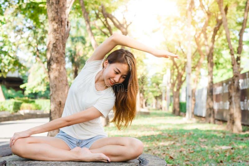 De jonge Aziatische vrouwenyoga houdt in openlucht kalm en mediteert terwijl het uitoefenen van yoga om de binnenvrede te onderzo royalty-vrije stock afbeelding