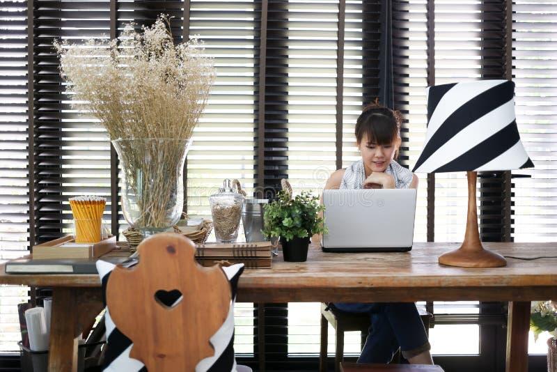 De jonge Aziatische werkende vrouw gebruikt laptop met wijnoogst decorat royalty-vrije stock foto's