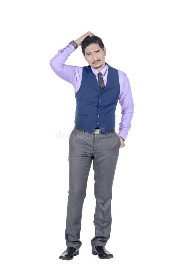 De jonge Aziatische zakenman die zijn hoofd krassen en kijkt verward stock foto