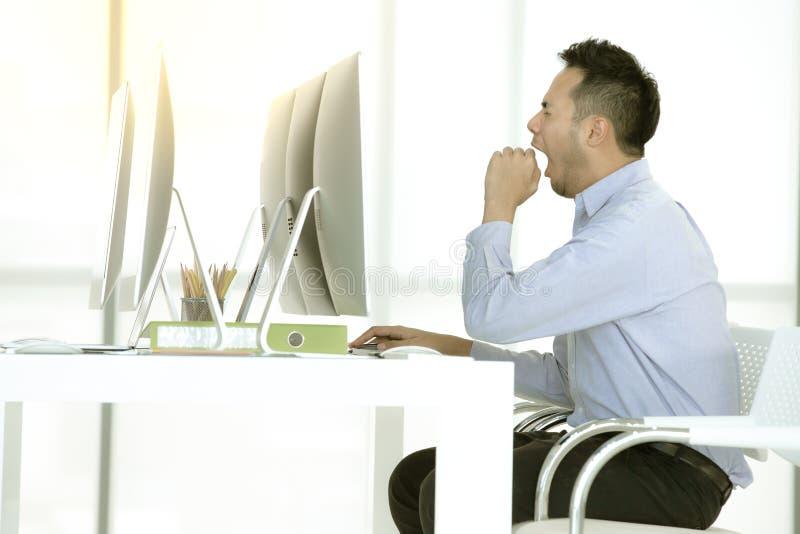 De jonge Aziatische zakenman zit en geeuw in modern bureau stock afbeelding