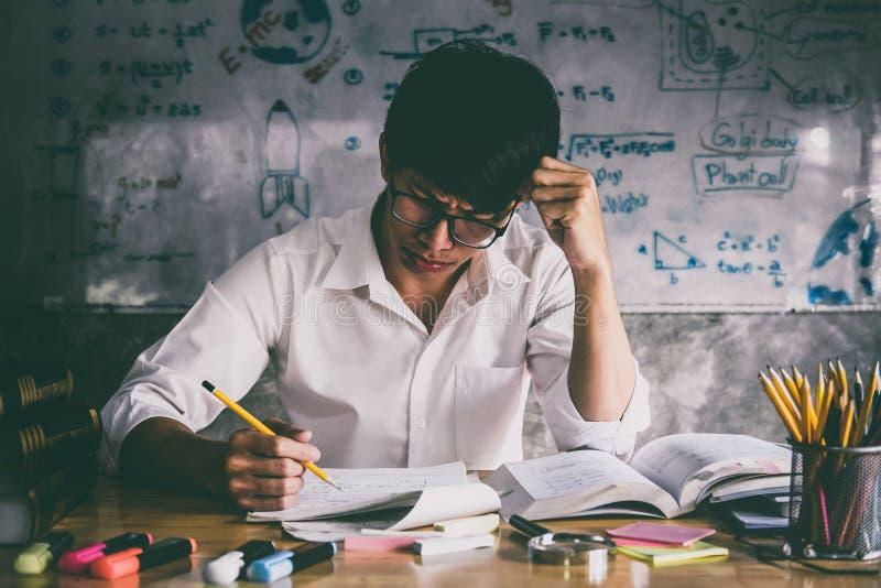 De jonge Aziatische zitting van de studentenmens bij bureau in huis het bestuderen en rea royalty-vrije stock afbeelding