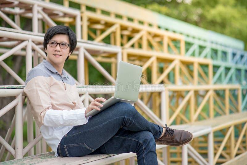 De jonge Aziatische zitting van de studentenmens op tribune die laptop met behulp van royalty-vrije stock afbeeldingen