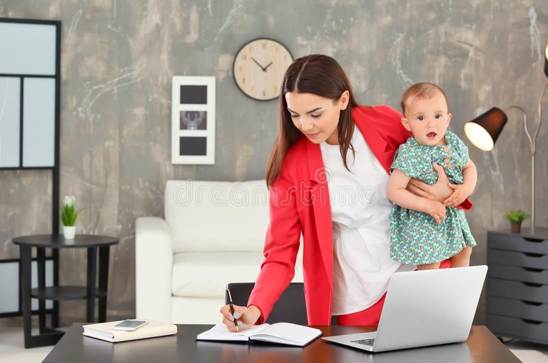 De jonge baby van de moederholding terwijl het werken in huis royalty-vrije stock fotografie