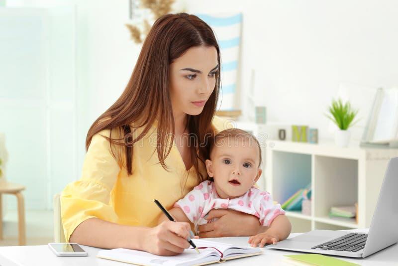 De jonge baby van de moederholding terwijl het werken in huis stock afbeeldingen