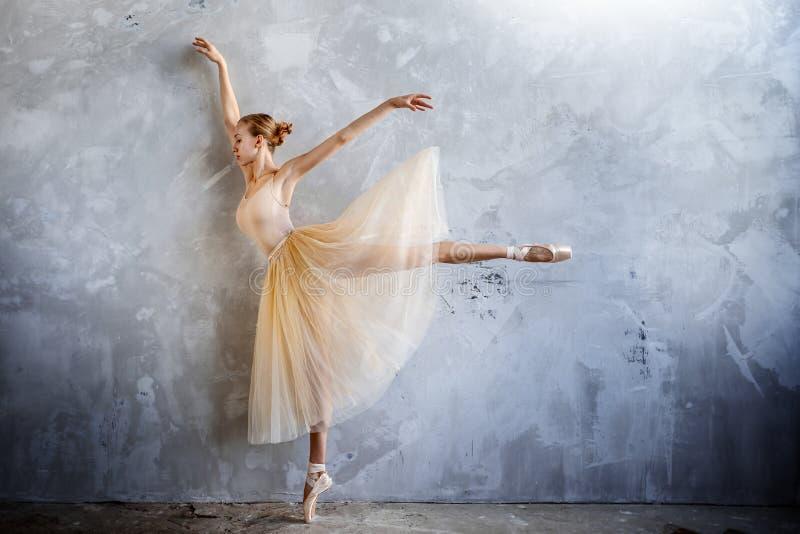 De jonge ballerina in een gouden gekleurd dansend kostuum stelt in een zolderstudio royalty-vrije stock afbeelding