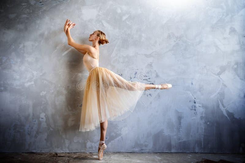 De jonge ballerina in een gouden gekleurd dansend kostuum stelt in een zolderstudio stock foto