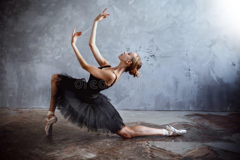 De jonge ballerina in een zwart dansend kostuum stelt in een zolderstudio royalty-vrije stock afbeelding