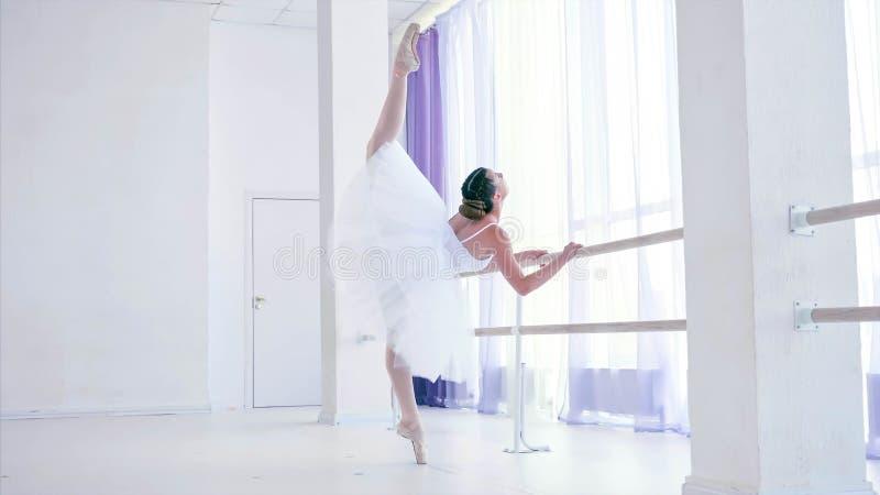 De jonge ballerina leidt balletelement dichtbij de staaftribune in op dansklasse stock afbeelding