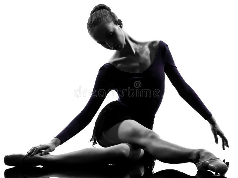 De jonge balletdanser die van de vrouwenballerina opwarmend silho uitrekken zich royalty-vrije stock foto's