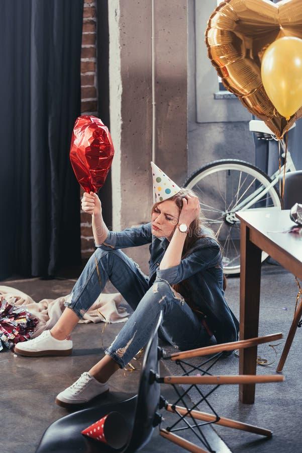 De jonge ballon van de vrouwenholding in slordige ruimte na partij stock fotografie