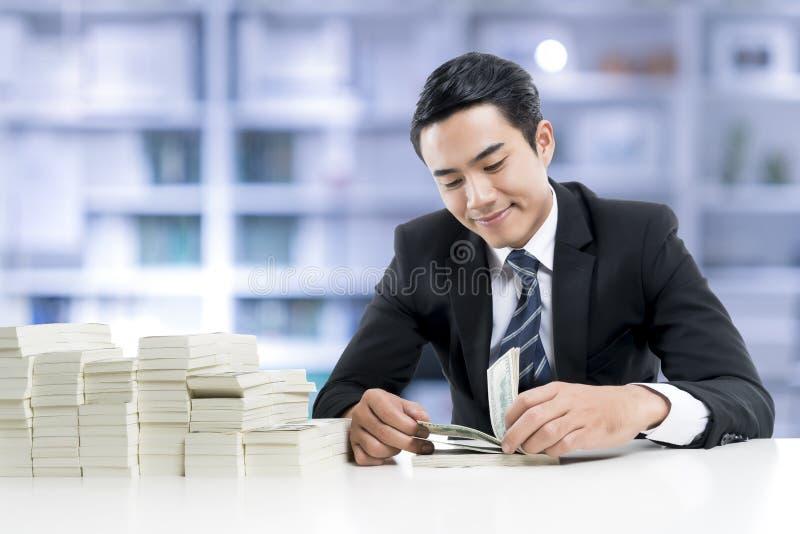 De jonge bankier telt bankbiljetten op de achtergrond van het bankbureau stock afbeeldingen