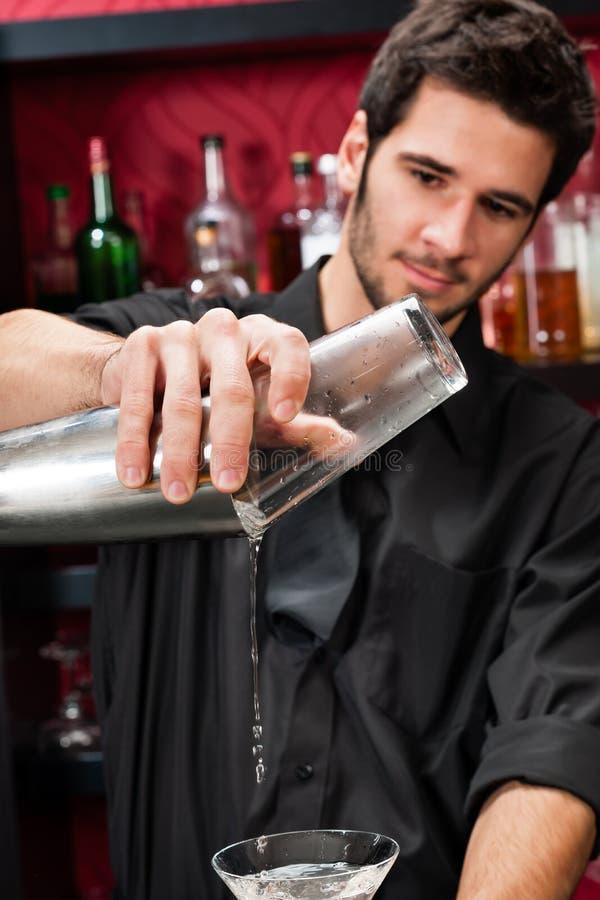 De jonge barman maakt cocktail het schudden dranken stock foto