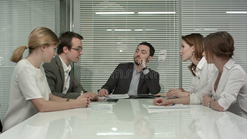 De jonge bedrijfsmensengroep heeft vergadering bij conferentieruimte en heeft discusion over nieuwe ideeënplannen en problemen stock foto