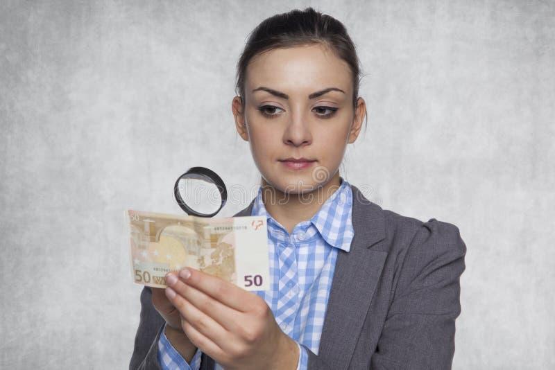 De jonge bedrijfsvrouw controleert de authenticiteit van geld stock fotografie