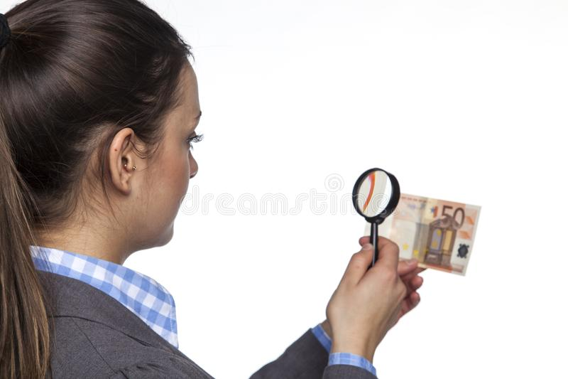 De jonge bedrijfsvrouw controleert de authenticiteit van geld op witte B stock afbeeldingen