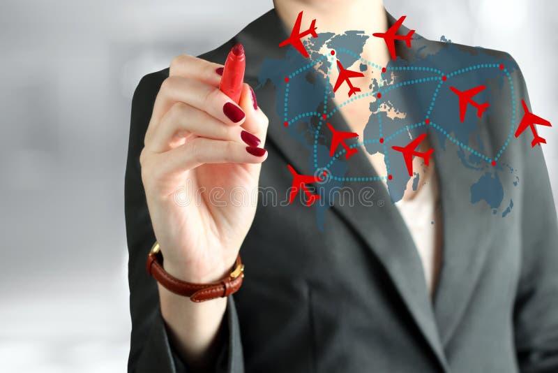 De jonge bedrijfsvrouw die een vliegtuig trekken leidt op wereldkaart royalty-vrije stock fotografie