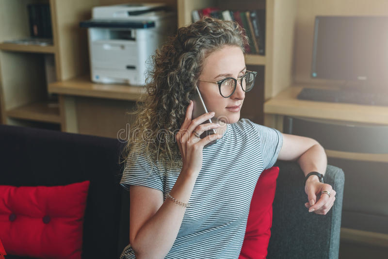 De jonge bedrijfsvrouw hipster in glazen zit op bank in bureau en spreekt op celtelefoon Telefoongesprekken royalty-vrije stock foto