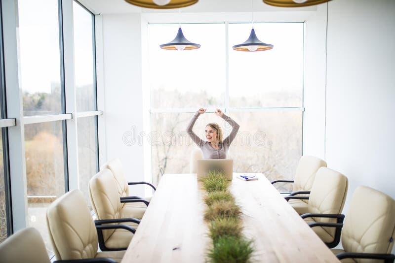 De jonge bedrijfsvrouw viert goede overeenkomstenoverwinning in bureau royalty-vrije stock foto's