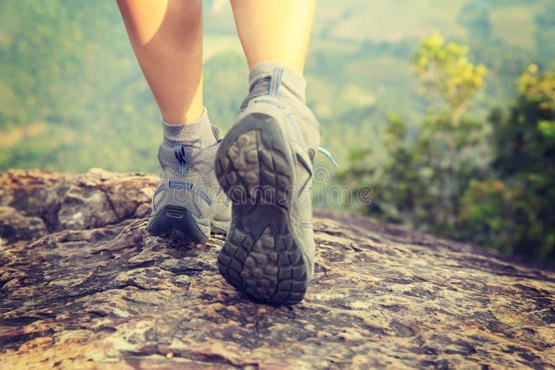 De jonge benen die van de vrouwenwandelaar bij bergpiek beklimmen royalty-vrije stock afbeelding