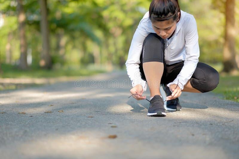 De jonge benen die van de geschiktheidsvrouw in de park openlucht, vrouwelijke agent op de weg buiten lopen, Aziatische atletenjo royalty-vrije stock afbeelding