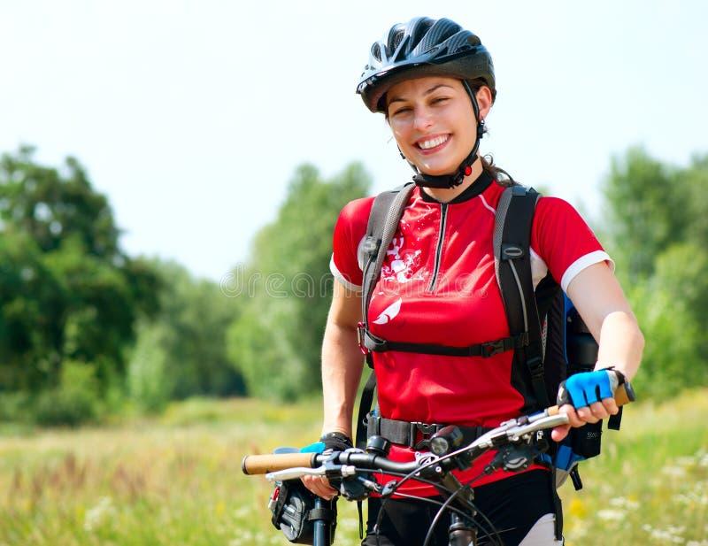 De jonge berijdende fiets van de Vrouw stock fotografie