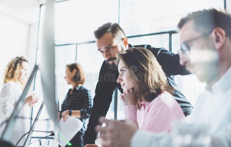 De jonge beroeps werken in modern bureau Het team die van de projectleider nieuw idee bespreken Commerciële bemanning die met ops