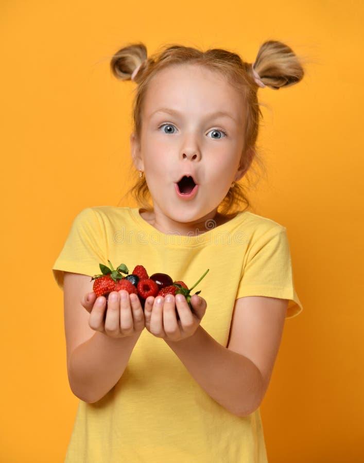 De jonge bessen van de het jonge geitjegreep van het babymeisje in handen verrasten het gelukkige het lachen gillen op geel royalty-vrije stock foto's