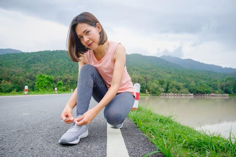 De jonge bindende loopschoenen van de Geschiktheidsvrouw in openbaar park, gezond levensstijlconcept stock foto's
