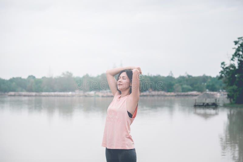 De jonge bindende loopschoenen van de Geschiktheidsvrouw in openbaar park, gezond levensstijlconcept royalty-vrije stock afbeelding