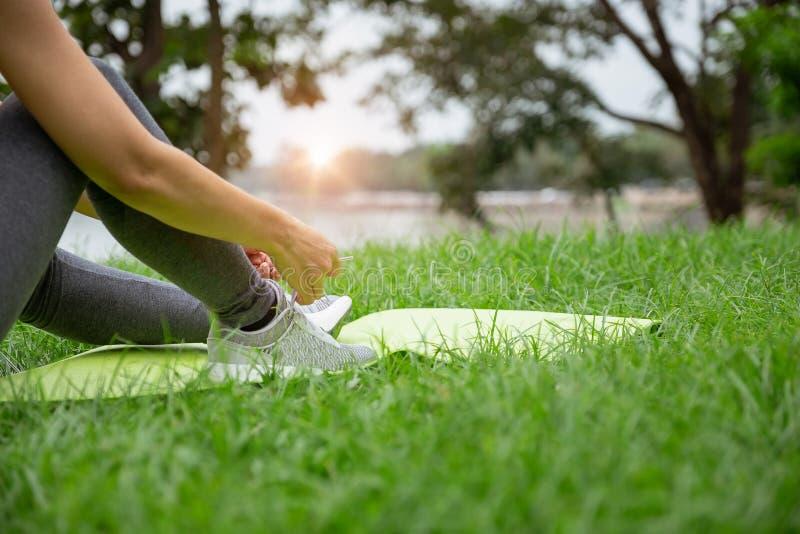 De jonge bindende loopschoenen van de Geschiktheidsvrouw in openbaar park, gezond levensstijlconcept stock afbeeldingen