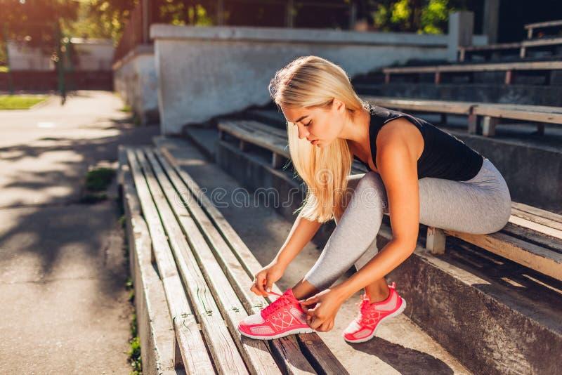 De jonge bindende tennisschoenen die van de vrouwenatleet op bank op sportsground in de zomer zitten Voorbereiding voor opleiding stock foto's