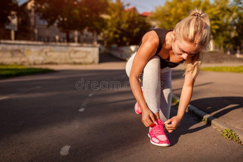 De jonge bindende tennisschoenen van de vrouwenatleet op renbaan op sportsground in de zomer Voorbereiding voor opleiding royalty-vrije stock foto