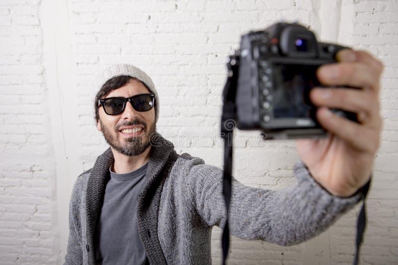 De jonge bloggermens hipster stileert de camera van de holdingsfoto schietend selfie video en foto stock afbeelding