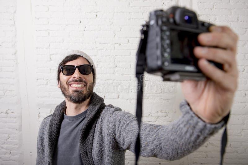 De jonge bloggermens hipster stileert de camera van de holdingsfoto schietend selfie video en foto royalty-vrije stock foto
