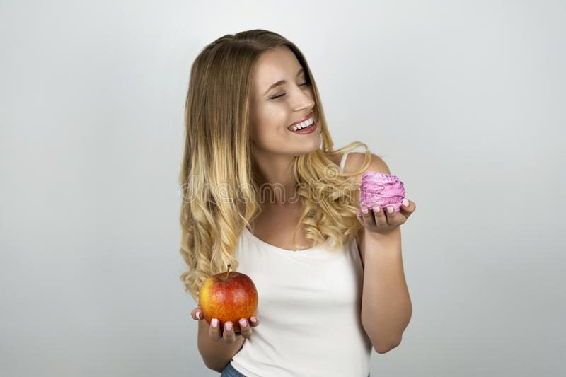 De jonge blonde aantrekkelijke vrouw die sappige rode appel in één hand en roze smakelijke cupcake in andere hand houden isoleerd royalty-vrije stock afbeelding