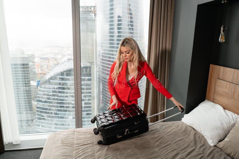 De jonge blonde onderneemster komt in een hotelruimte aan met zwarte koffer E Jong meisje royalty-vrije stock afbeelding