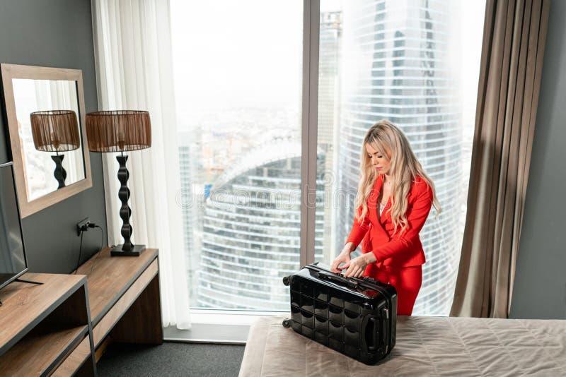 De jonge blonde onderneemster komt in een hotelruimte aan met zwarte koffer E Jong meisje stock fotografie
